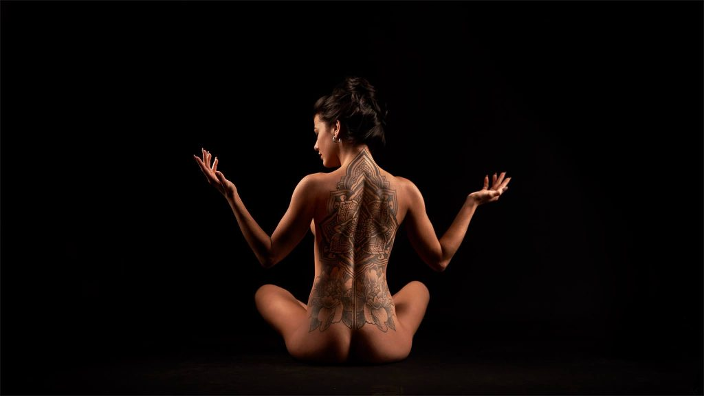 Boudoir- seated nude woman with back tattoo looking to the side